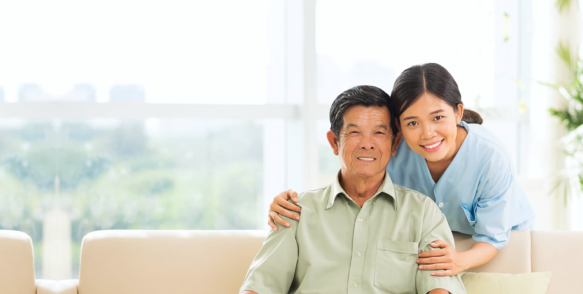 caregiver and senior man sitting on the sofa smiling