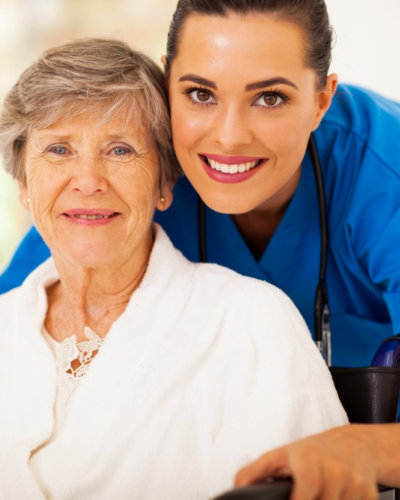 senior woman on wheelchair with nurse wearing stethoscope smiling
