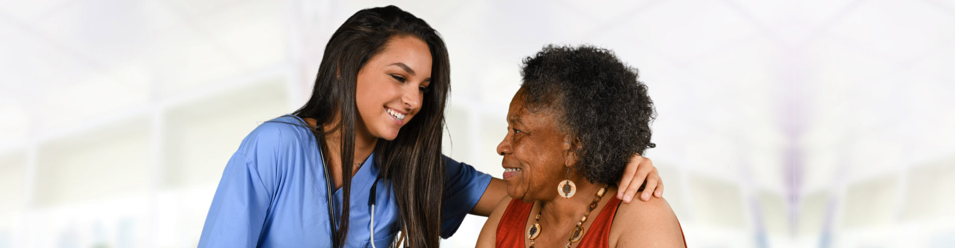 female nurse and senior woman smiling