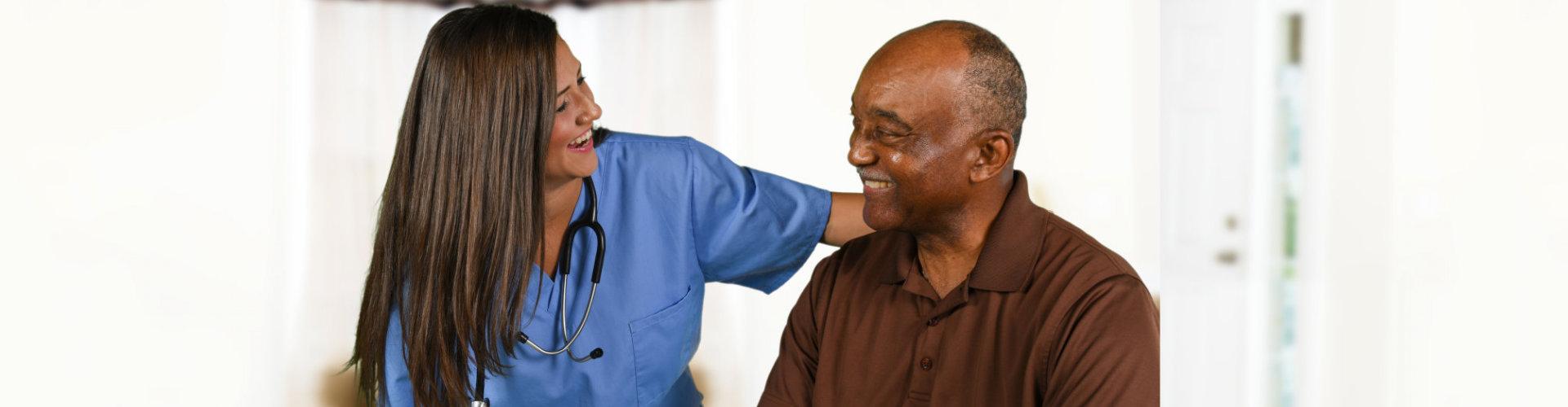 female nurse wearing stethoscope and senior man smiling