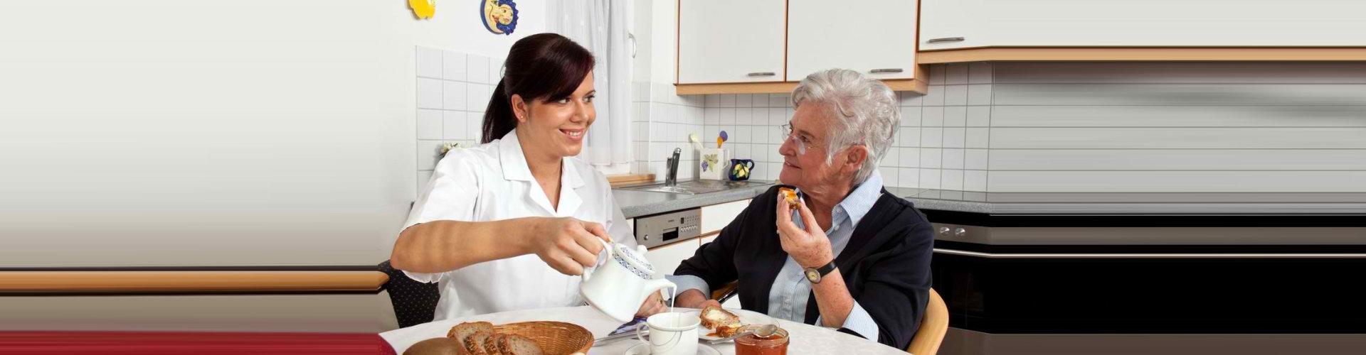 caregiver preparing meals to senior woman wearing eyeglasses smiling
